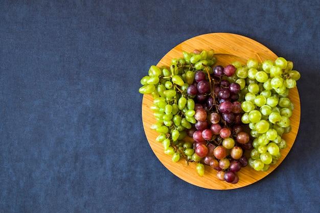 Jesienne winogrona na niebieskim stole, zbieranie owoców sezonowych