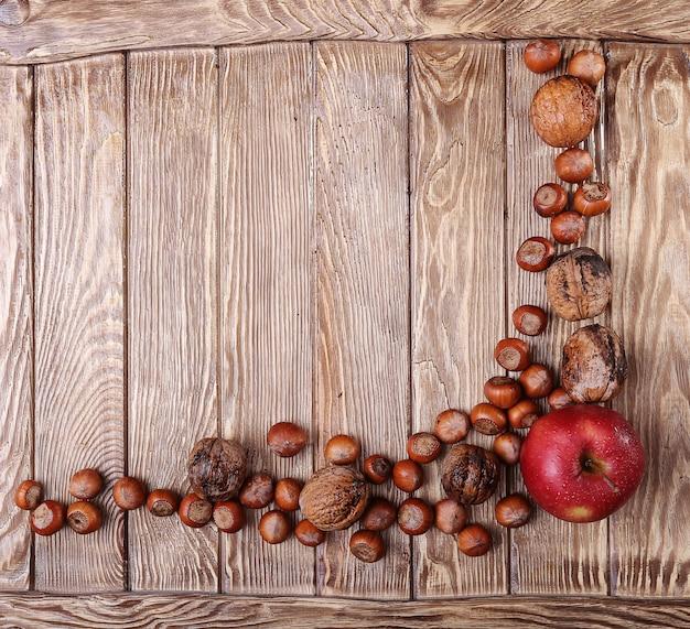 Jesienne zbiory. jabłko i dokrętki na drewnianym stole