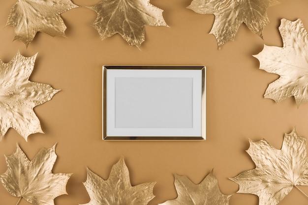 Jesienne złote liście klonu i ramki na białym tle na beż