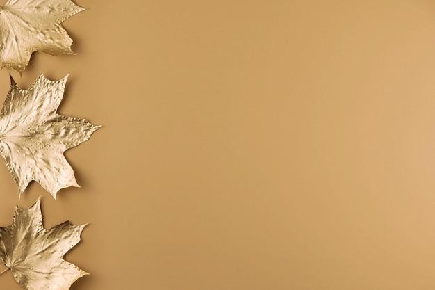 Jesienne złote liście klonu na białym tle na beż