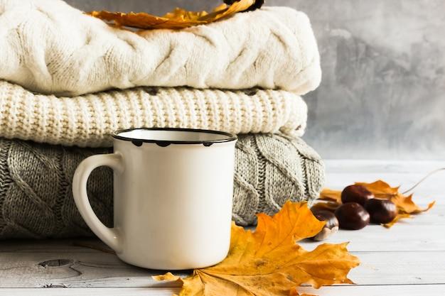 Jesienne żółte liście klonu, szyszki, kasztany, biały kubek i przytulne swetry z dzianiny na szarym tle