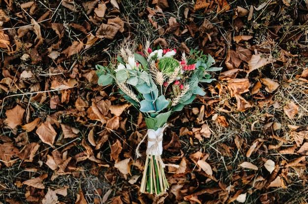 Jesienny bukiet ślubny z żółtych i pomarańczowych kwiatów, czerwone jagody leżące na trawie w jesiennych liściach.