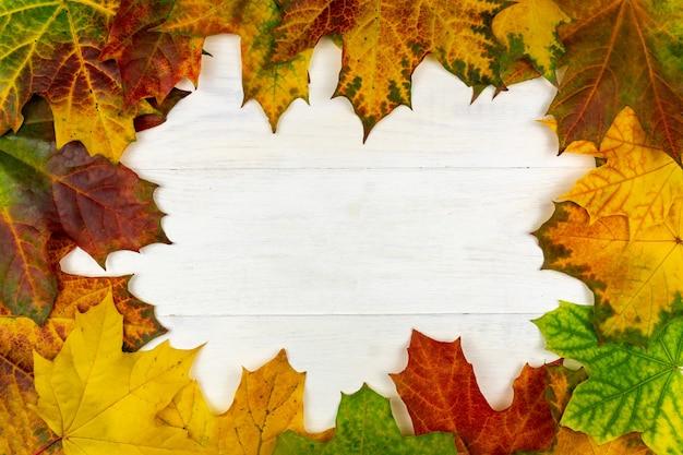 Jesienny bukiet suchych liści klonu na drewnianym stole. rama.