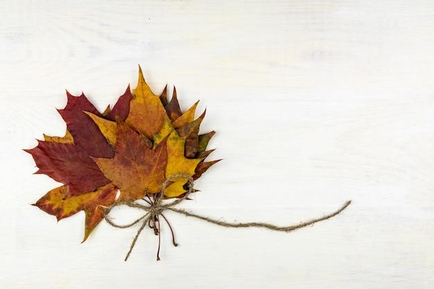 Jesienny bukiet suchych liści klonu na drewnianym
