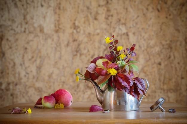 Jesienny bukiet w żelaznym czajniczku na drewnianym stole