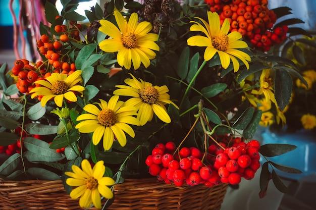 Jesienny bukiet z kwiatów aster i suchych liści. żółte stokrotki i czerwony popiół w koszyku