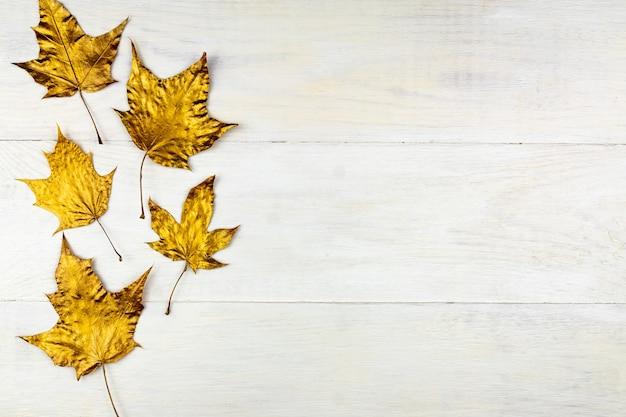 Jesienny bukiet z liści klonu pomalowanego na złoty kolor na drewnianym tle
