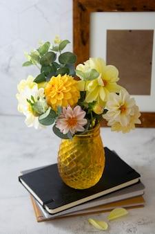 Jesienny bukiet ze świeżych kwiatów dalii na zeszytach
