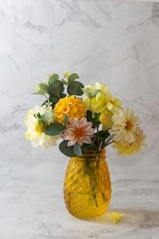 Jesienny bukiet ze świeżych kwiatów dalii w żółtym szklanym wazonie.