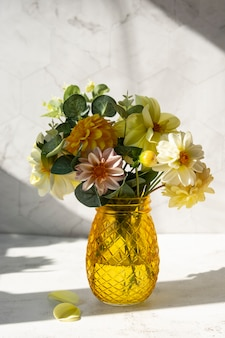 Jesienny bukiet ze świeżych kwiatów dalii ze światłem słonecznym i cieniami.