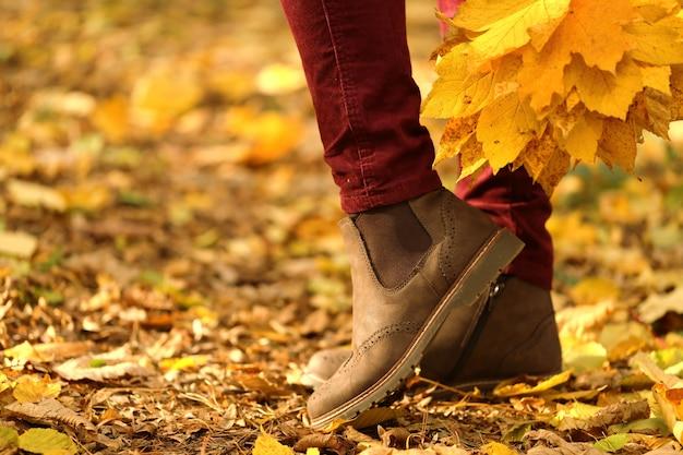 Jesienny czas. kobiece nogi w brązowych zamszowych butach na żółtych liściach. modne jesienne buty