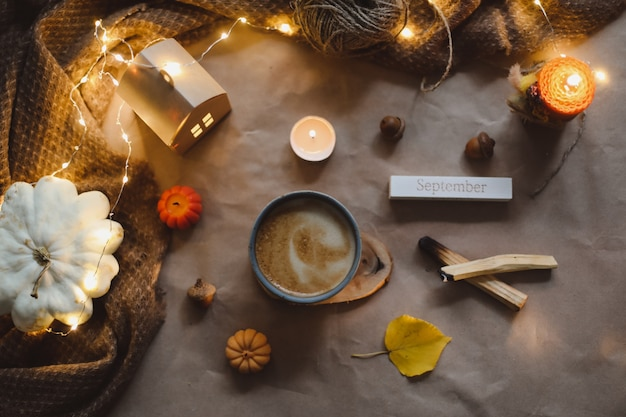 Jesienny czas przytulny wystrój domu hygge z filiżanką świec w kratę halloween i koncepcja dziękczynienia