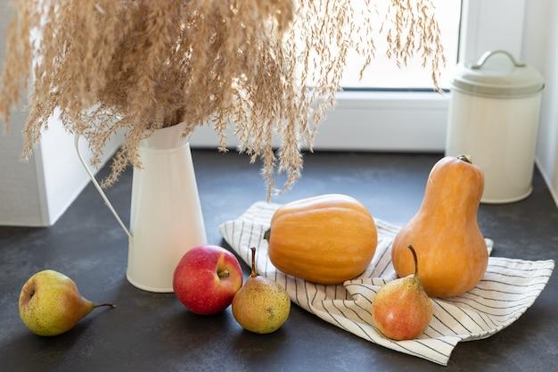 Jesienny dom martwa natura dynie jabłka gruszki i trawa pampasowa na kuchennym blacie