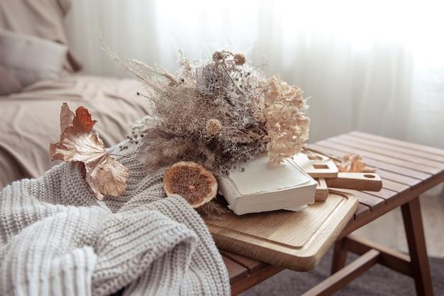 Jesienny klimat dzięki jesiennym dekoracjom i sweterowi z dzianiny w pokoju.