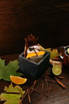 Jesienny koktajl cytrusowy w kamiennym pudełku na stole w restauracji