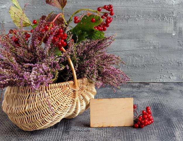 Jesienny kosz martwej natury z wrzosem i kaliną i pustą pocztówką dzięki podziękowaniu