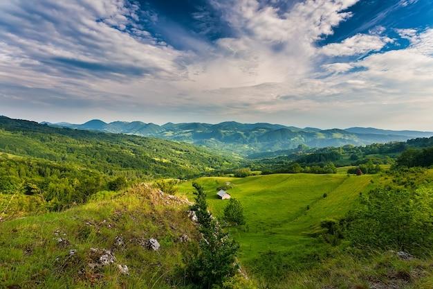 Jesienny krajobraz górski - pożółkłe i zaczerwienione jesienne drzewa połączone z zielonymi igłami i błękitnym niebem. kolorowa jesień krajobrazowa scena w rumuńskich karpatach. widok panoramiczny.