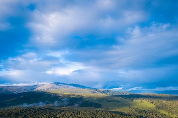 Jesienny krajobraz górski rejon ałtaj chemalski: wysokie góry, las, pokryte chmurami. panorama gór.