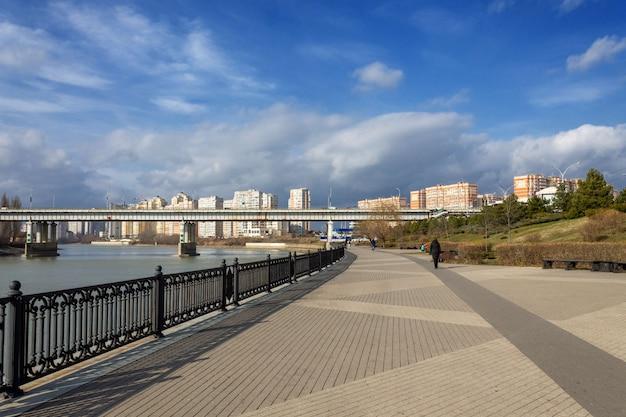Jesienny krajobraz ludzie spacerują wzdłuż nabrzeża rzeki kubań i widokiem na most turgieniewski w jesienny poranek w mieście krasnodar