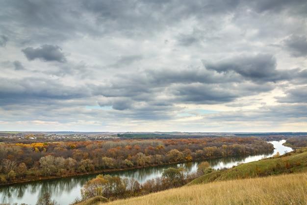 Jesienny krajobraz na wzgórzach rzeki don. widok na staw na tle zachmurzonego nieba ...