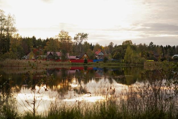 Jesienny krajobraz wiejskich domów na brzegu stawu odbijający się w wodzie o zachodzie słońca rosja