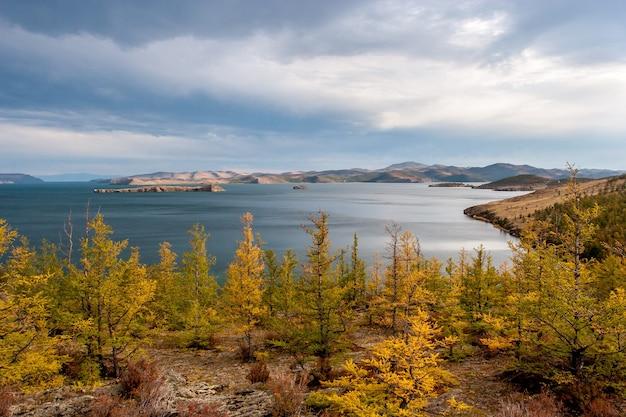 Jesienny krajobraz z drzewami i widokiem na jezioro bajkał, żółte drzewa na pierwszym planie i chmury na niebie