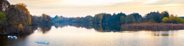 Jesienny krajobraz z rzeką i drzewami o zachodzie słońca, panorama