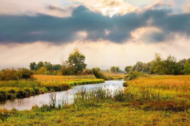 Jesienny krajobraz z rzeką i malowniczym dramatycznym niebem podczas zachodu słońca