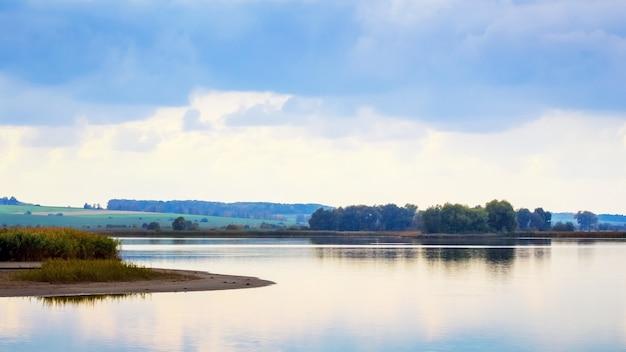Jesienny krajobraz z szeroką rzeką i odbiciem chmur w wodzie