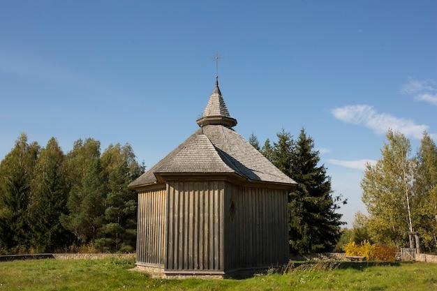 Jesienny krajobraz. żółte liście na drzewach i rustykalny drewniany kościół. zdjęcie wysokiej jakości