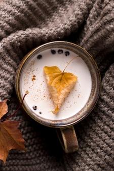 Jesienny napój mleczny owinięty w szalik z liściem w środku.