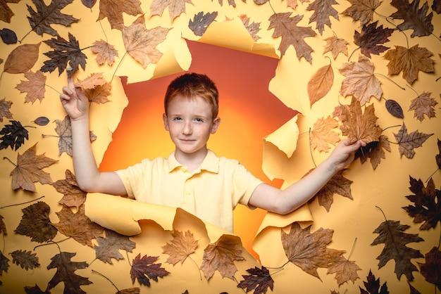 Jesienny nastrój i pogoda jest ciepła i słoneczna, a deszcz jest możliwy. chłopiec w sezonowych ubraniach ze złotymi listkami.