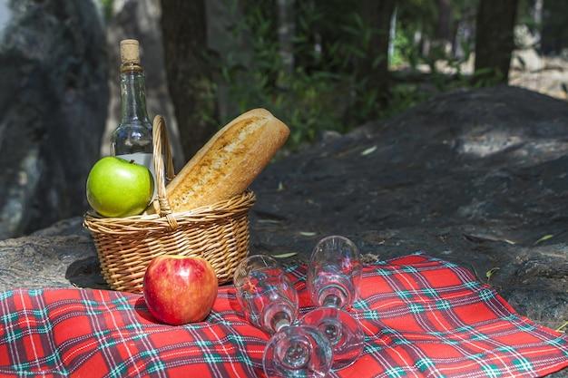 Jesienny obiad piknikowy. wiklinowy kosz z bagietką, winem i jabłkami