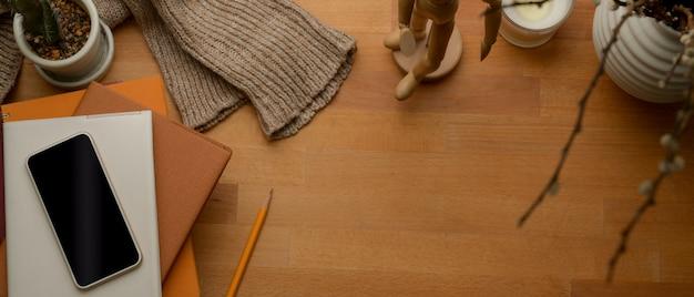 Jesienny obszar roboczy z miejsca na kopię, smartfon, notebooki, sweter i dekoracje na drewnianym stole