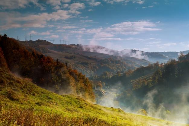 Jesienny pagórkowaty krajobraz pokryty zalegającą mgłą z ciepłym światłem poranka.
