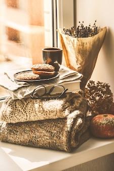 Jesienny parapet tło z książek, kawy i ciasteczka.