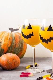 Jesienny pomarańczowy wakacyjny koktajl z dyni z wystrojem halloween na stole.