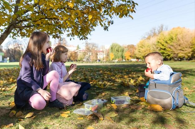 Jesienny portret dzieci z lunch boxami, plecakami szkolnymi
