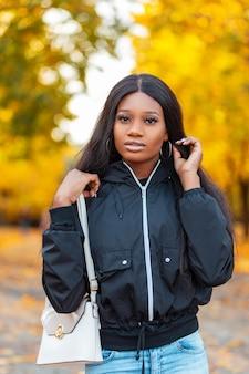 Jesienny portret ładnej czarnej amerykanki w stylowej casualowej kurtce ze skórzaną torbą spaceruje po jesiennym parku z kolorowymi żółtymi jesiennymi liśćmi
