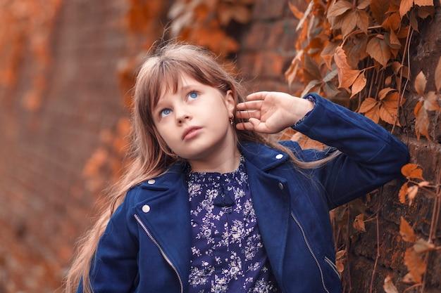 Jesienny portret mała piękna dziewczyna w pobliżu kamiennego muru wygląda na boki marzycielsko