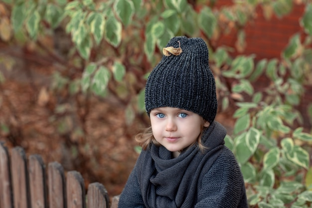 Jesienny portret małej dziewczynki na tle liści w szarym ciepłym dzianinowym kapeluszu i szaliku