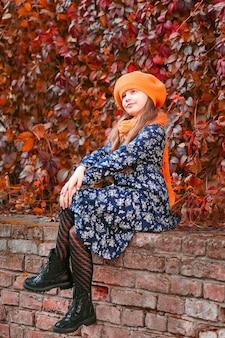 Jesienny portret małej dziewczynki piękna dziewczyna w żółtym berecie na tle czerwonych liści