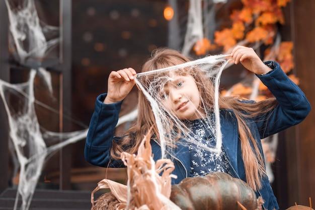Jesienny portret małej dziewczynki trzymającej pajęczynę na tle dekoracji halloween