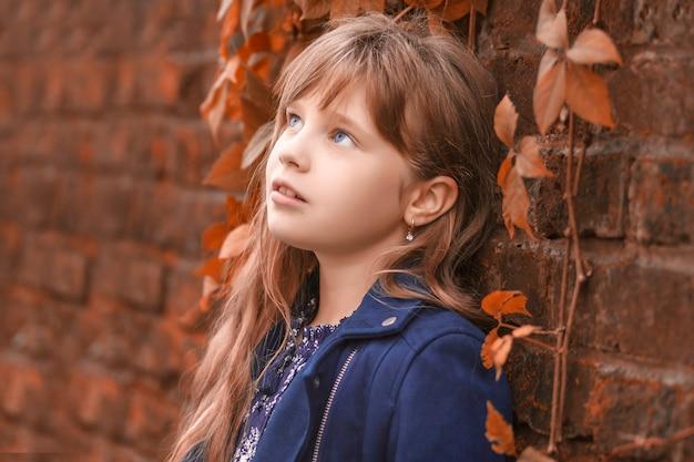 Jesienny portret małej marzycielskiej dziewczynki w pobliżu kamiennego muru z pożółkłymi liśćmi