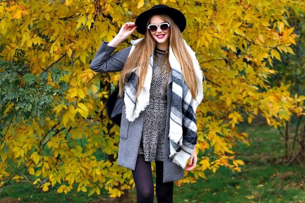 Jesienny portret mody oszałamiającej eleganckiej modelki pozującej w parku, złotych liści i chłodnej pogodzie, luksusowych ubrań w stylu ulicznym, jasnego makijażu, dużego szalika, mini sukienki nakłada się na płaszcz i vintage kapelusz.