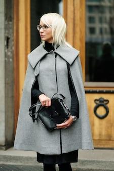 Jesienny portret pięknej blondynki w szarym płaszczu z czarną torbą