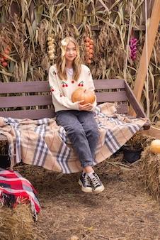 Jesienny portret pięknej dziewczyny z dynią na halloween w pobliżu domu