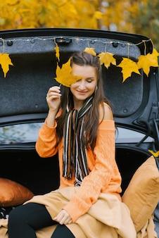 Jesienny portret pięknej kobiety brunetka jesienią parkl siedzi na bagażniku