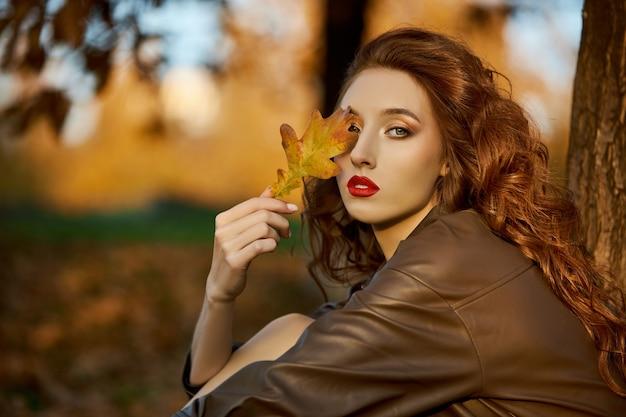 Jesienny portret rudowłosej kobiety w przyrodzie w świetle zachodu słońca.