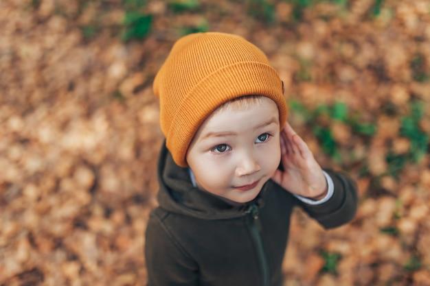 Jesienny sezon mody dla dzieci, odzież dla dziecka w kapeluszu, chłopiec z jesiennymi liśćmi, trzy lata